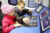 MOSCOW, RUSSIA - JAN 1, 2014: Happy boy and girl sit at control panel of subway train simulator.