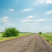 asphalt road in green fields and blue cloudy sky