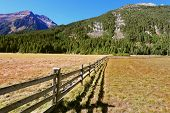 Alpine Valley in Austria. National Park Krimml waterfalls. Scenic farm fields blocked by the wooden