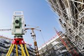 surveyors measuring instrument, close-ups, large super-wide construction site in background