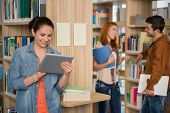 University student looking at tablet with classmates talking in library