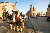 KRAKOW, POLAND - FEB 26, 2014: Carriages at Main Market Square. It dates to the 13th century, and at
