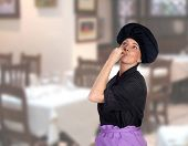 Woman making the gesture cook delicious in the restaurant