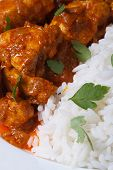 stock photo of chinese parsley  - Rice and chunks of chicken curry on a plate macro vertical - JPG