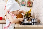 stock photo of apron  - Little girl in apron and cap of the cook stands in the kitchen near cooker in the house - JPG