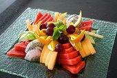image of fruit platter  - Colorful summer fruit platter with watermelon cantaloupe grapes oranges Dragon fruit and mint