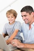 Happy father reaching son to use laptop at home