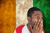 Nervous football fan looking ahead against ivory coast flag in grunge effect