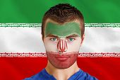Composite image of serious young iran fan with facepaint against digitally generated iran national f