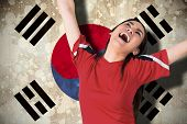 Composite image of excited asian football fan cheering against south korea flag