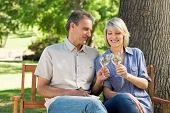 Loving couple toasting wine glasses while sitting on bench in a park