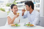 Happy couple having a meal together with white wine outside on a balcony