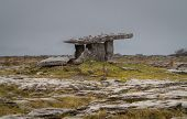 stock photo of burial  - Poulnabrone Dolmen burial chamber near Burren in Eire on a grey cloudy day - JPG