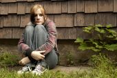 image of runaway  - A teenage girl with a sad expression sits against a run - JPG