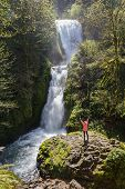 stock photo of bridal veil  - attractive woman standing in on a rock with bridal veil falls on the side Oregon USA - JPG