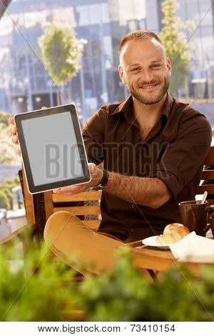 Happy man sitting outdoors, holding tablet computer with blank screen, smiling, looking at camera.