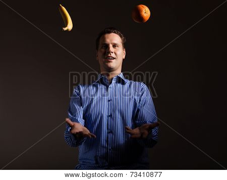 Diet Nutrition. Man Juggling With Tropical Fruits