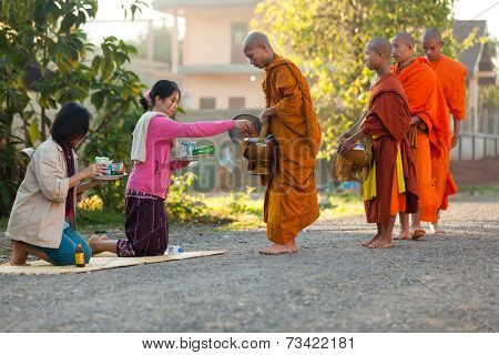 VANG VIENG, LAOS, MARCH 19, 2011: women giving daily food at the Buddhist monks during early morning traditional alms in the village of Viang Vieng, Laos