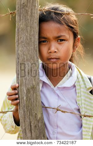 SAYABURY, LAOS, FEBRUARY 16, 2012: Laotian little girl posing near a fence pole in the schoolyard during the Elefantasia festival in Sayaboury, Laos