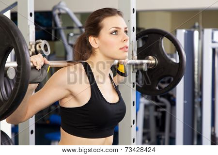 Young slim woman exercising in a gym