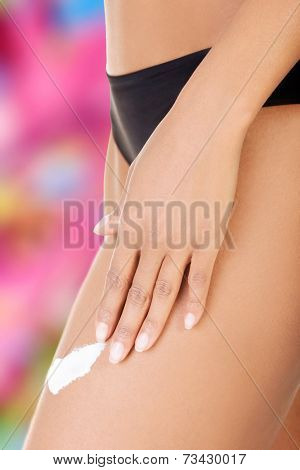 Female smooth legs with one hand lotioning. Closeup