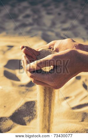 Tinted Image Sand Pours Out Of The Female Hands