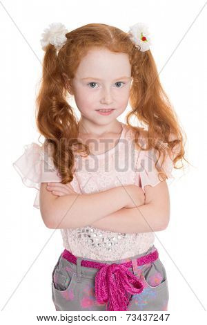 Portrait of a six years old girl with red hair with arms crossed.