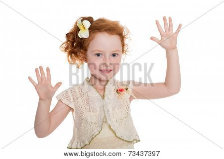 Little girl with hands raised. The girl is six years old.