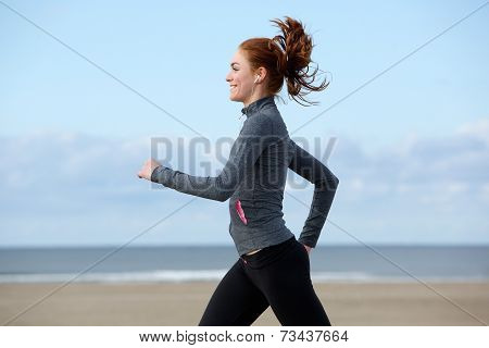 Beautiful Young Woman Exercising By The Beach