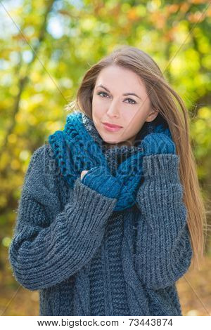 Trendy woman in warm autumn fashion snuggling down into her blue polo neck jersey and scarf while walking outdoors in a park