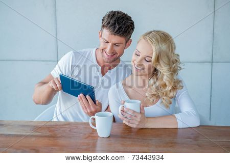 Happy couple surfing the web on a tablet smiling as they read something on the screen together while enjoying their morning coffee