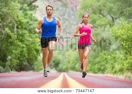 Running young people - two runners jogging on road in nature training for marathon run. Multicultural couple - asian mixed race beautiful model woman and caucasian male fitness model exercising