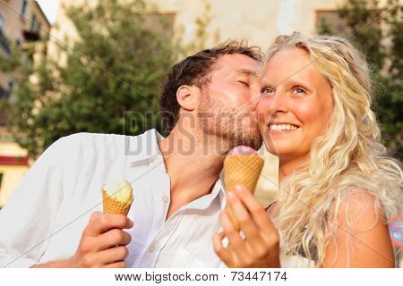 Couple eating ice cream kissing happy having fun in love enjoying summer romance in city. Happy romantic woman and man eating ice cream cone outdoors in summer on travel holidays vacation.
