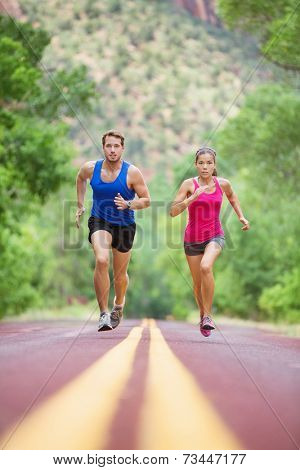 Running young mixed race couple sprinting concentrated on road outside in nature exercising jogging sport. Pretty asian model and caucasian male model.