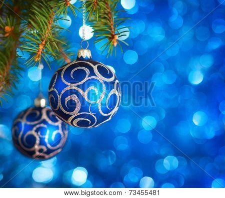Christmas Baubles on light blue background with sparkles .