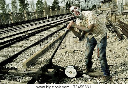a scary zombie operating the railroad switch of the railroad tracks