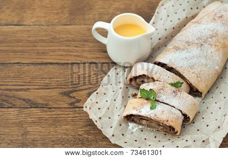 Apple strudel with vanilla sauce on wooden background.