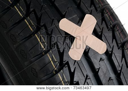 black new tire with patch on white