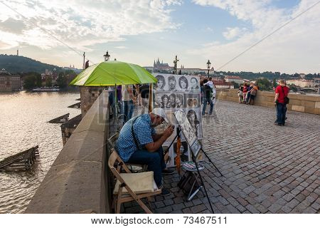 Cartoonist takes a break during his shift on Charles bridge, Prague