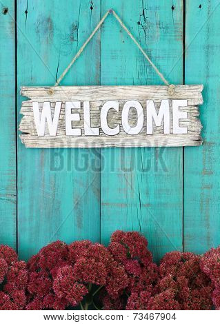 Rustic wooden welcome sign hanging on antique teal blue door with border of fall flowers