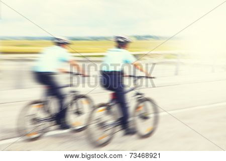 Blurred image of police officers on bicycles in motion.