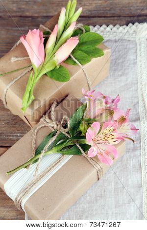 Natural style handcrafted gift boxes with fresh plants and rustic twine, on wooden