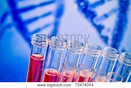 Closeup Of Test Tubes With Red Liquid On Abstract Dna Background