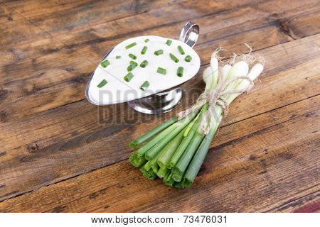 Metal bowl of cream with a tuft of onion near it on wooden background