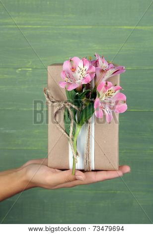 Female hand holding natural style handcrafted gift box with fresh flowers and rustic twine, on wooden background