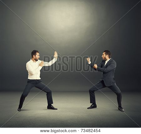 battle between two young businessmen in the dark studio