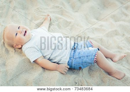 Cute baby lying down on a sand
