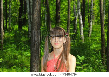 Girl in red dress walks in the woods