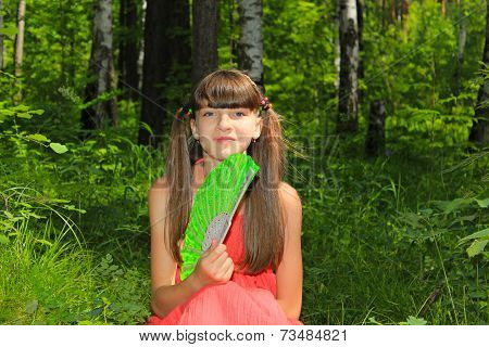 Girl sitting in the forest with a fan