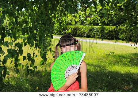 Girl on the nature of the person covers green fan